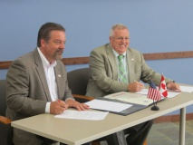 Photo: Jeff Holt (left), Board Chair of the Sault Ste. Marie [Michigan] Economic Development Corporation, and Don Mitchell, President and Board Chair of the Sault Ste. Marie [Ontario] Economic Development Corporation, sign the memorandum of understanding.