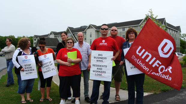 Members of Unifor Local 1359 stand outside MapleView on Northern Ave. Thursday