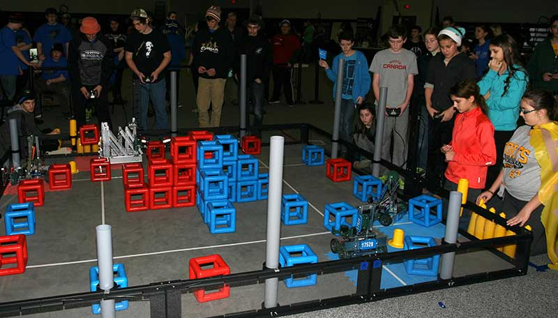 Semi-final play with four robots starting off their match.  Teams gained points by stacking the yellow SkyRise pieces into a tower, and also stacking the coloured cubes onto perimeter tubes or their Skyrise towers.