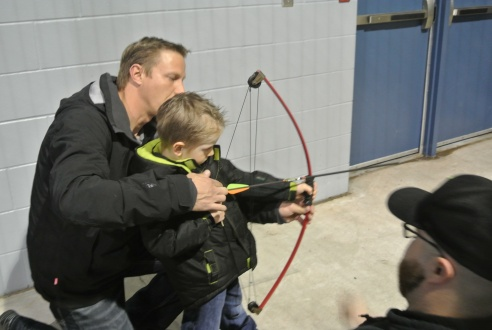 This young tyke is getting a lesson from his son about the proper way to hold a bow and arrow