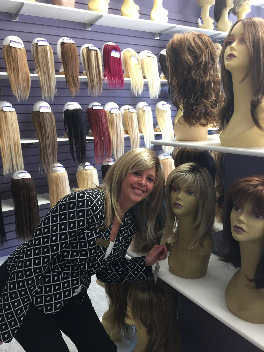 Gail Giardino, store owner. stands beside a model of the wig she is currently wearing.