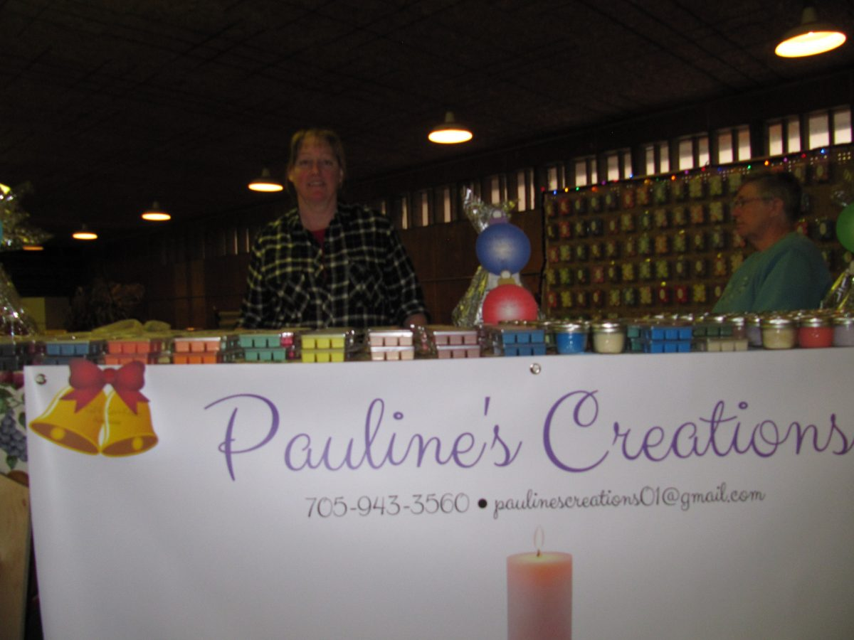 Pauline stands behind the new logo and banner created by her team of students
