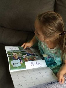 Ashley checking out her picture in the calendar.
